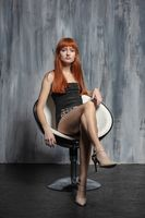 Beautiful lady posing sitting on a chair
