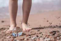 Boy feet and glass ball on the beach