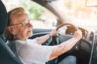 Elderly woman behind the steering wheel of a car