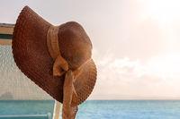 Female sunhat with ribbon on beach chair.