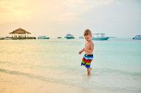 Three year old toddler boy on beach at sunset