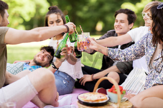 friends clinking drinks at picnic in summer park