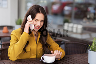 teenage girl calling on smartphone at city cafe