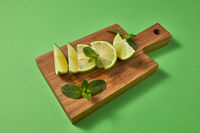 Slices of fresh green lime and sprig of green mint on a wooden brown board on a green. Ingredient for homemade lemonade.
