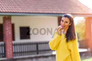 A beautiful woman eating a Apple in Autumn