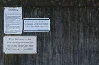 Friedhofordnung an grauer Mauer