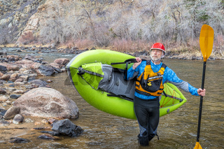 senior paddler carrying  inflatable whitewater kayak