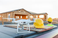 Drone Quadcopter Next to Hard Hat Helmet At Construction Site with Worker Behind
