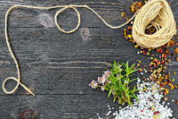 Thyme leaves and flowers with twine on black wooden board