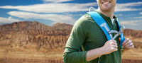 close up of man with backpack over grand canyon