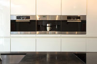 Elegant and modern white kitchen interior with oven and coffee machine close-up clean and luxury interior