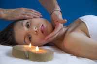 spa, attractive brunette spanish girl getting a massage on her face and neck by a massage professional