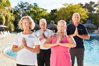 Senioren machen eine Yoga Übung am Pool