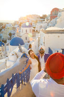 Indian tourists taking photos of colorful Oia village on Santorini island, Greece.