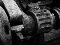 monochrome image of rusted cogs and gears on an old abandoned broken industrial machinery