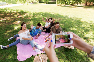 friends photographing by smartphone at picnic