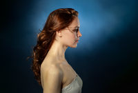 Beauty fashion portrait. Young woman on blue wall background.