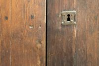 Rusted keyhole over an old wooden grunge door