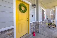 yellow front door with rocking chair