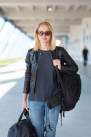 Portrait of young cheerful female traveler wearing casual clothes carrying heavy backpack and luggage at airport.