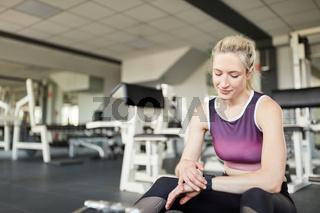 Sportliche junge Frau schaut auf ihre Smart Watch