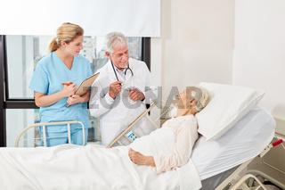 Arzt am Bett einer kranken Seniorin