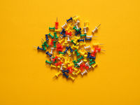 Colorful pushpins on yellow