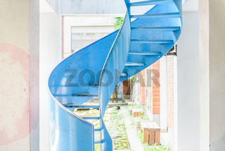 Shabby metal spiral ladder in bright room