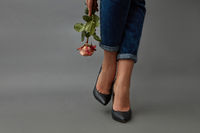 Legs of a woman in jeans and black high-heeled shoes next to a girl's hand holds a pink rose around a dark background with space for text. Beautiful modern composition