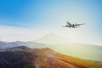 airplane flying on sunset sky background  - travel concept -