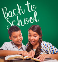 Back To School Written On Chalk Board Behind Hispanic Boy and Girl Having Fun Studying Together