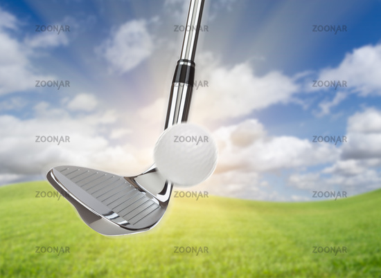Chrome Golf Club Wedge Iron Hitting Golf Ball Against Grass and Blue Sky Background