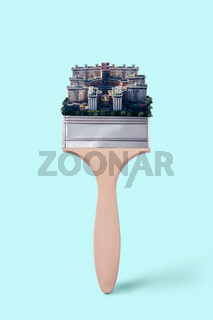 Creative paint brush with town houses on a turquoise color Pantone background, copy space. Painting cityscape.