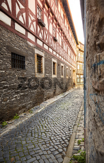 Narrow cobbled street between half-timbered houses in historical city center of Erfurt