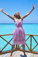 Young beautiful girl jumps in pink sundress on platform of villa on water