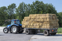 Blue tractor with plain old farm wagon with straw bales stacked