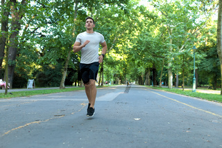 A handsome young man jogging in a park