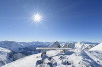 Bench on Karwendel mountainrange with sun in winter