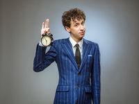 Business man holding alarm clock