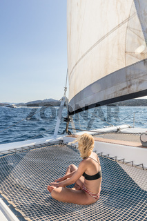 Beautiful woman relaxing on a summer sailing cruise, relaxing and sunbathing in hammock of luxury catamaran sailing around Maddalena Archipelago, Sardinia, Italy in warm afternoon light