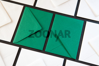 Composition with white and green envelopes on the table.