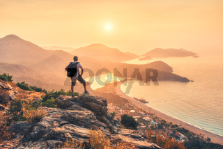 Young sporty man with backpack, seashore and mountains