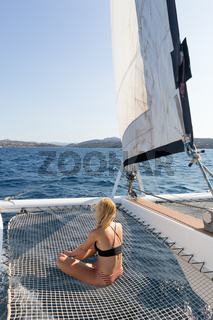 Beautiful woman relaxing on a summer sailing cruise, sitting and sunbathing in hammock of luxury catamaran sailing around Maddalena Archipelago, Sardinia, Italy in warm afternoon light