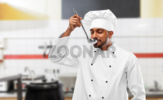 happy indian chef tasting food by ladle at kitchen