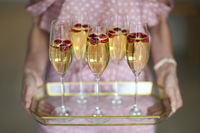 Young woman with champagne glasses on tray