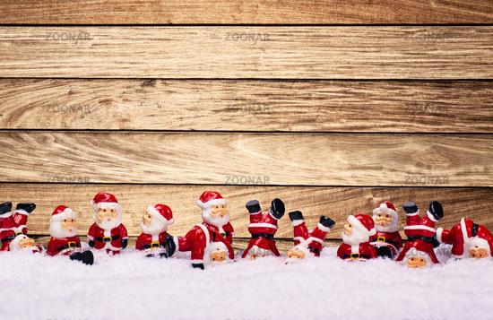 Weihnachtsmänner vor Holzwand