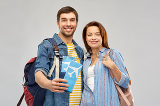 happy couple with air tickets, bags and passport