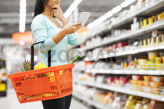 woman with food in shopping basket at supermarket