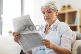 senior woman reading newspaper at home