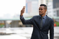 Happy young African businessman taking selfie in the city streets outdoors